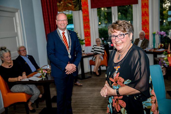 Miny van der Zande draagt vol trots het lintje waarmee burgemeester Ton Heerts haar tijdens het afscheidsetentje van Vereniging Oud Apeldoorn kwam brengen.