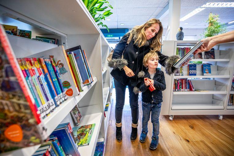 In de bibliotheek van Wognum zoeken moeder en zoon naar het juiste boek.   Beeld Raymond Rutting / de Volkskrant