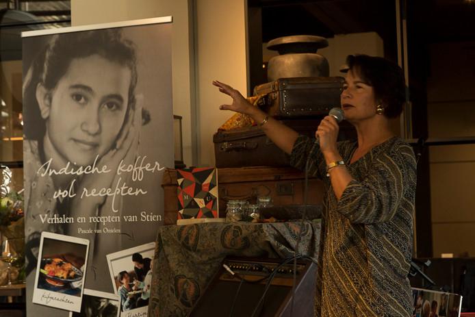 Schrijfster en kleindochter Pascale van Onselen tijdens de boeklancering van 'Indische koffer vol recepten'. Op de foto op de achtergrond is de jonge Stien Boermeester te zien.