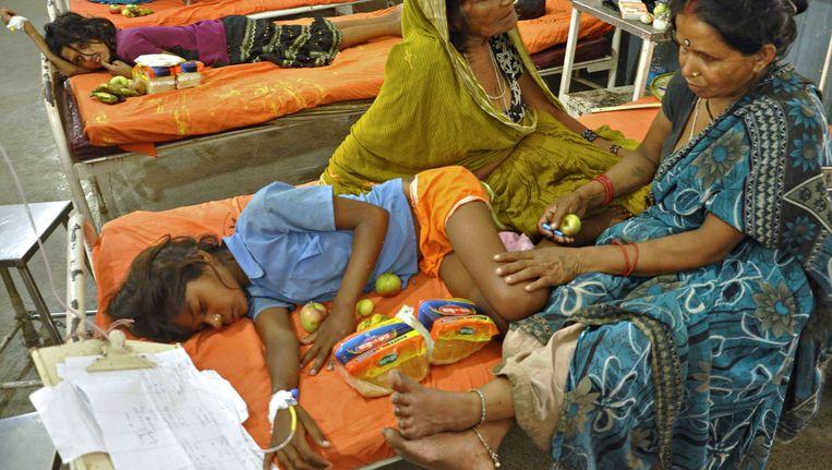Een van de slachtoffertjes van de vergiftigde schoolmaaltijd in het ziekenhuis van Bihar Beeld AFP