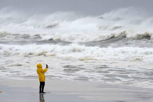 Een durfal neemt foto's in de branding van Okaloosa Island, nabij het stand van Fort Walton.