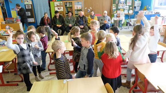 Terwijl de leerlingen volop bezig zijn, kijken de ouders aandachtig toe.