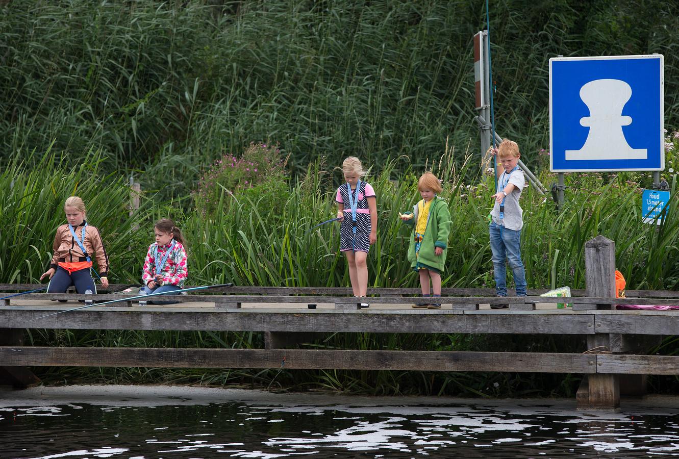 Kinderen krijgen les in sportvissen tijdens de viskaravaan bij sluizencomplex De Pol.