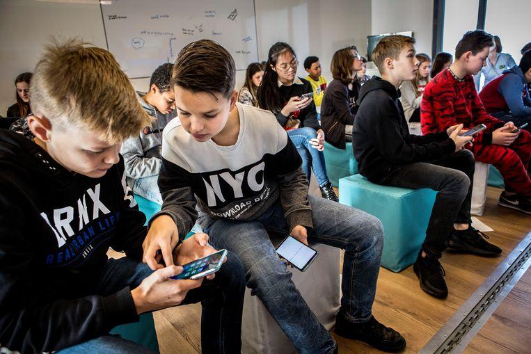 Kinderen aan het werk in het mobiele klaslokaal in de Smartbus van Huawei. Beeld Arie Kievit
