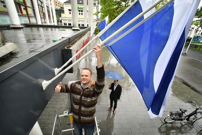 Ben van Veen met de Hengelose vlag bij de schouwburg.