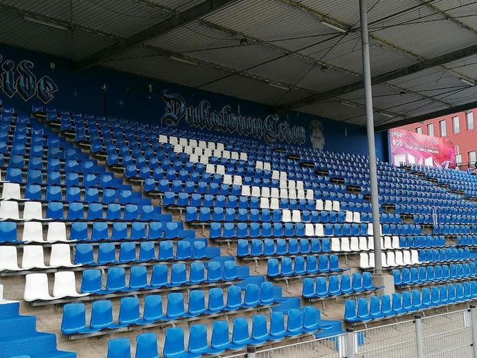 Alle rode stoeltjes zijn blauw geverfd op de Oosttribune van de Vliert.