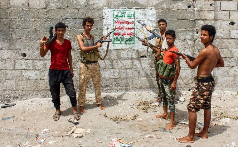 Strijders van de eenheid Gigant richten hun kalasjnikovs op een Houthi-muurschildering waarop staat: God is de grootste... dood aan Amerika, dood aan Israël, vervloekt zijn de joden, de zege is aan de islam. In Hodeida. Beeld Saleh Al Obeidi / AFP