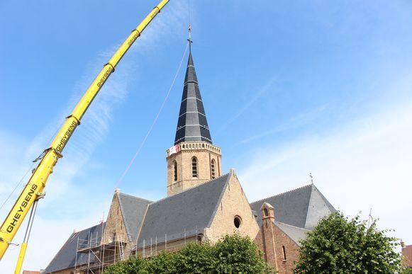 Een kraan plaatst het laatste stuk van de toren op de Sint-Niklaaskerk.