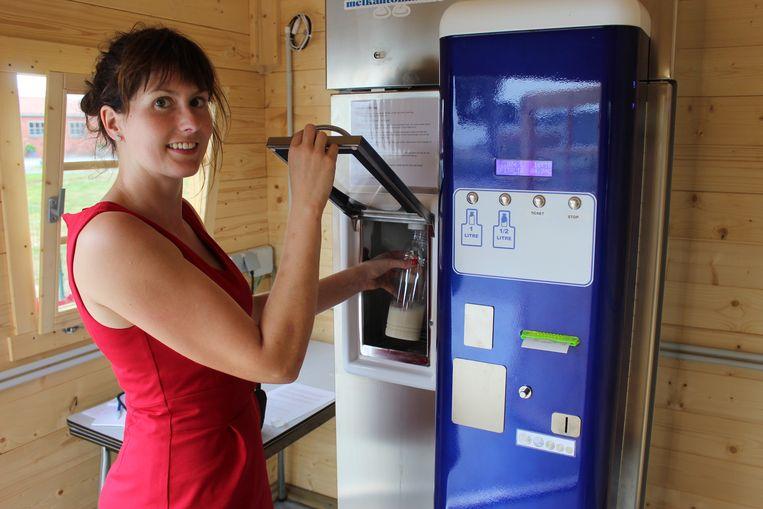 Elien Almey demonstreert de melkautomaat.