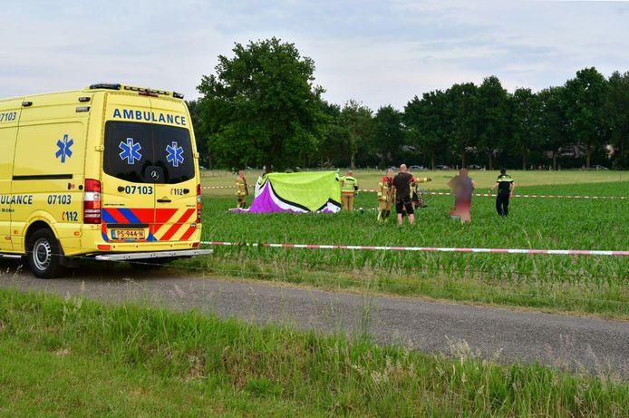 Hulpdiensten ontfermen zich over de neergestorte paraglider in Didam.