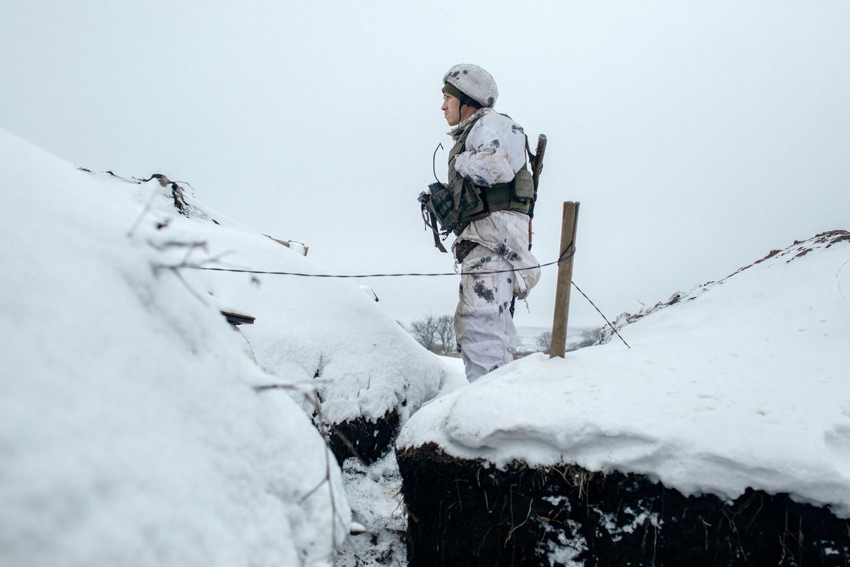 Een Oekraïense militair staat in een loopgraaf bij het dorp Zelote, zijn blik gericht op het gebied waar de door Rusland gesteunde separatisten heersen.   Beeld Emile Ducke