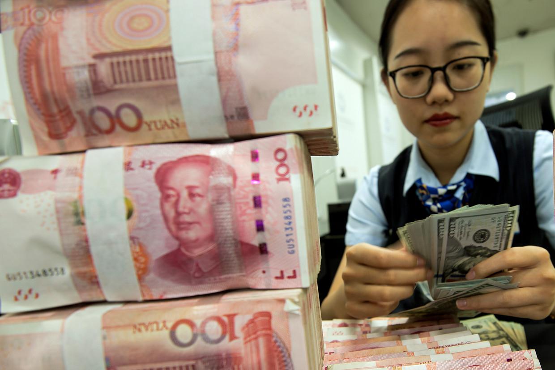 Een Chinese bankmedewerker telt dollarbiljetten naast een stapel met briefjes van 100 yuan.   Beeld AP