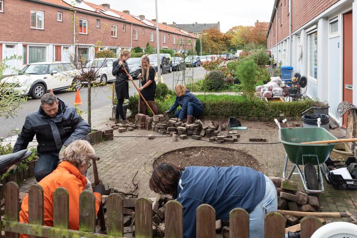 De tuin van Wilma van de Weerd wordt ontsteend. Vanaf links met de klok mee Frits Steemers, studentes Esther Kieft en Gerda van de Weerd, Corina Boonzaaijer, Evelien Beukema en Femke Oosterveld.