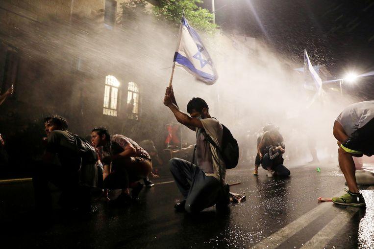 De Israëlische politie zet een waterkanon in bij een van de vele demonstraties tegen premier Netanyahu deze week in Jeruzalem. Beeld Reuters