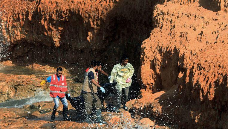 Libische hulpverleners halen een lichaam van een illegale migrant die aan een kust in Tripoli aanspoelde, uit het water.
