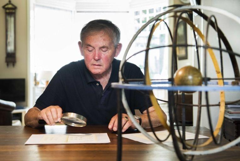 Henk Thate kijkt naar een kopie van het oude meteorologische dagboek van zijn vader. Beeld ANP