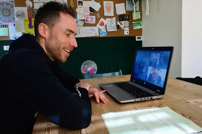 Docent Iroy Cosse thuis achter zijn laptop in gesprek met leerlingen.