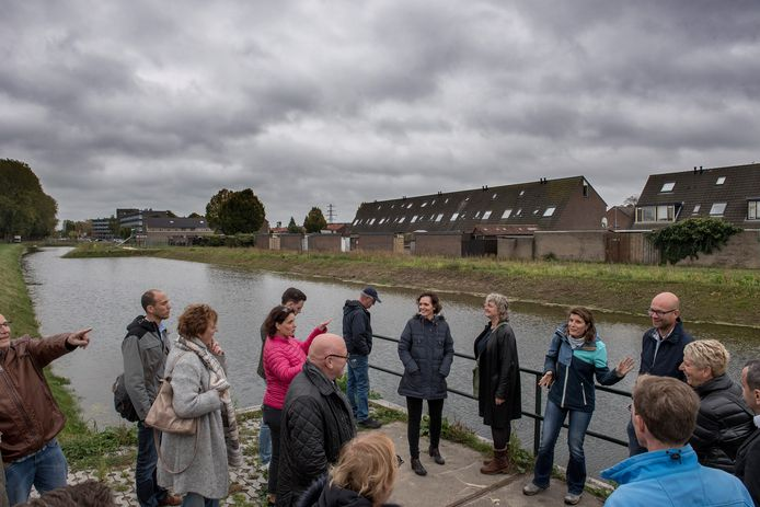 Bezoekers nemen een kijkje bij de nieuwe waterberging aan de Spoorsingel in Tiel-Oost.