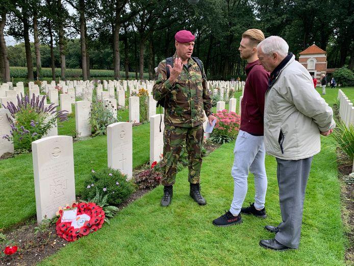 Max Clark en zijn opa (rechts) krijgen uitleg van de gids op de begraafplaats .