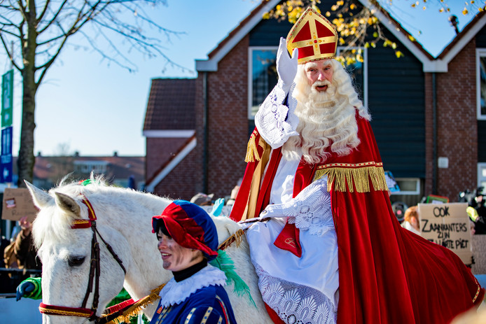 Sinterklaas tijdens de intocht in Zaanstad in 2018. Op de achtergrond anti-piet demonstranten.