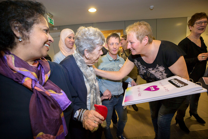 Oudere bewoonster komt Nanon van der Veen steunen bij de overhandiging van het witboek met ervaringen van werkneemsters van Thebe dat zij samenstelde.
