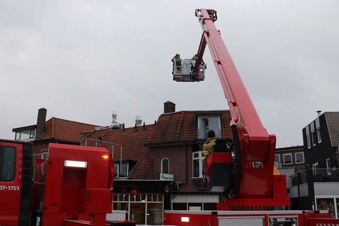 De brandweer zet een plaat vast op het dak van restaurant De Hebbert aan de Jan van Schaffelaarstraat in Barneveld.