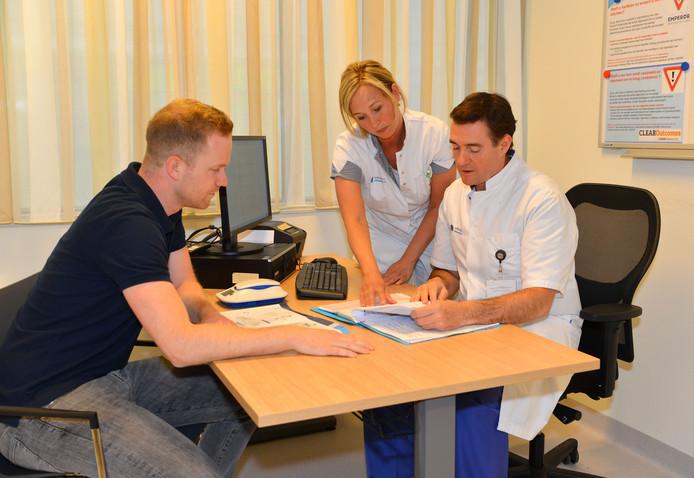 Cardioloog Tim Simmers (rechts), verpleegkundige Claire Vredegoor en patiënt Rob Zwekars over monitoring op afstand in het Eindhovense Catharina Ziekenhuis.