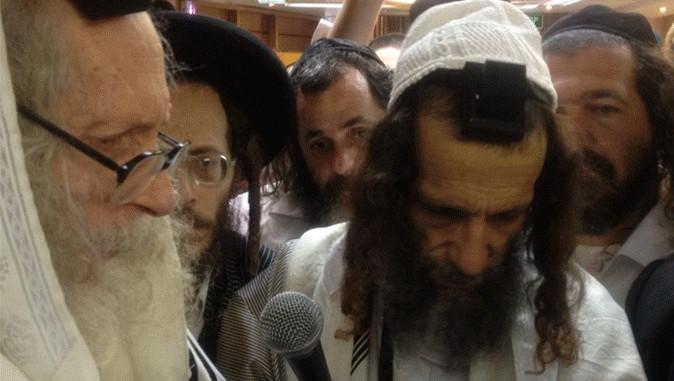 Rabijn en sekteleider Eliezer Berland (links met grijze baard) omringd door enkele volgelingen.