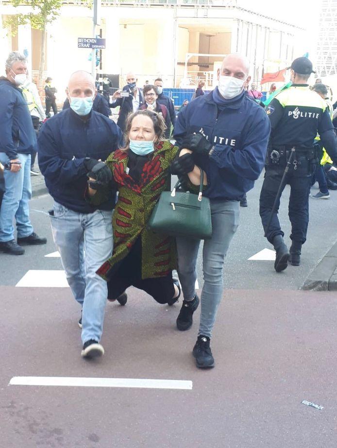Een demonstrant wordt afgevoerd door de politie.