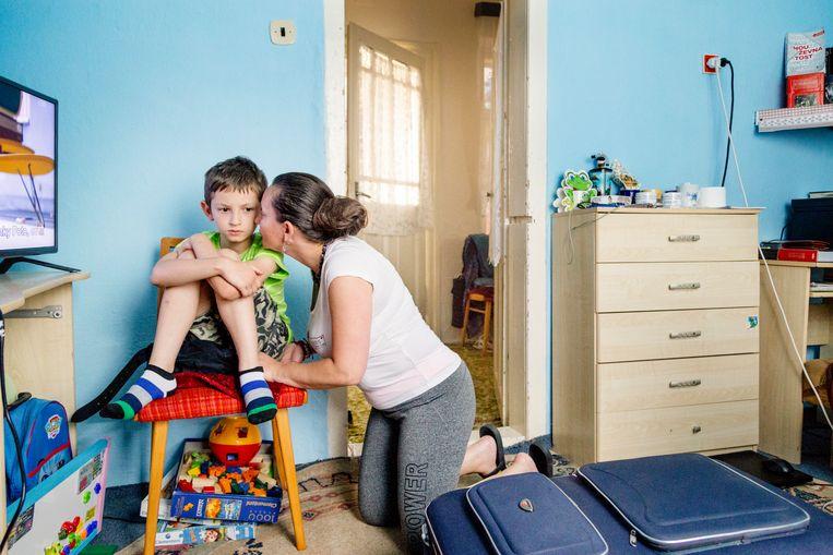 Moeder Maria geeft Eriks broertje Enrico een kus op zijn wang. Enrico is autistisch en gaat naar een speciale school in Košice.   Beeld null