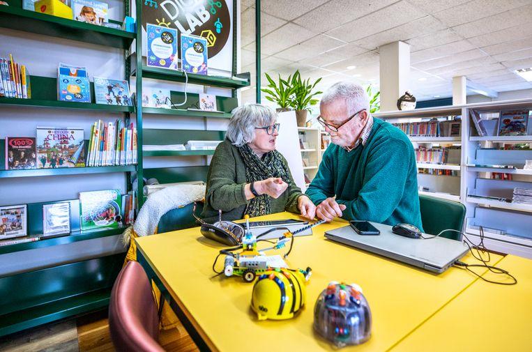 In de bibliotheek van Wognum geeft een vrijwilliger uitleg over de werking van een tablet. Beeld Raymond Rutting / de Volkskrant