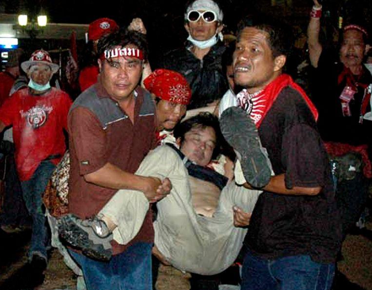 De rode betogers dragen de zwaargewonde Muramoto, die sterft voor hij in het ziekenhuis aankomt.