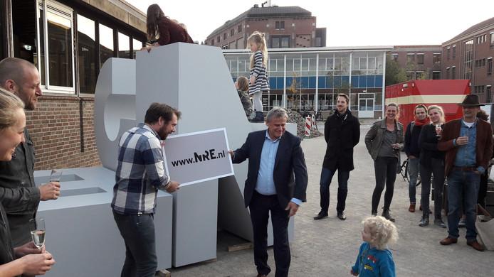 Ton Schuurmans van Enexis (rechts) 'overhandigt' de site www.nre.nl aan Bas Koreman, lid van creatief collectief NulZes op het NRE-terrein. Achter hen het letterkunstwerk dat symbool staat voor de gezamenlijke identeit. Later moet dat een definitieve vorm krijgen. Links Renee Scheepers en Dirk Smits van NulZes.