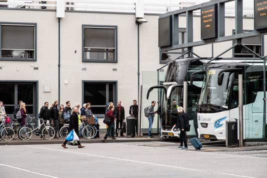 Reizigers in de rij voor de bussen op station Nijmegen.