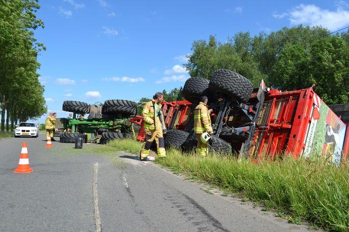 De tractor en silagewagen liggen gekanteld in de berm naast de weg.