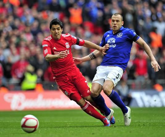 John Heitinga (r) namens Everton in duel met Luis Suárez.