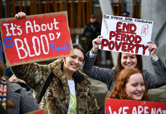 Activisten die voor de ondertekening van de wet zijn demonstreren bij het Schotse parlement.