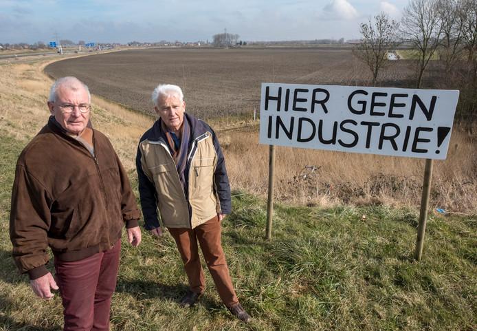 Hans van Hal (rechts) en John de Rijke van de Werkgroep Trekdijk staan voor het stuk land waar een bedrijventerrein moet komen.