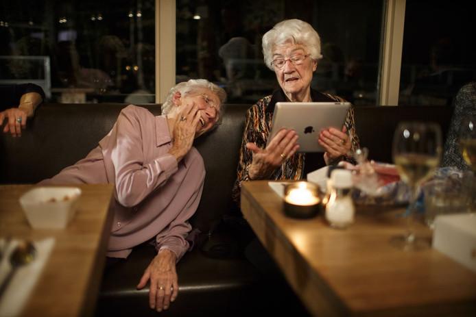 Eef Arnolds-Bakker heeft een iPad gekregen voor haar 94e verjaardag. Ze vieren het in een restaurant. Samen met haar zus (links) heeft ze een live gesprek via Skype met een nicht in het buitenland.