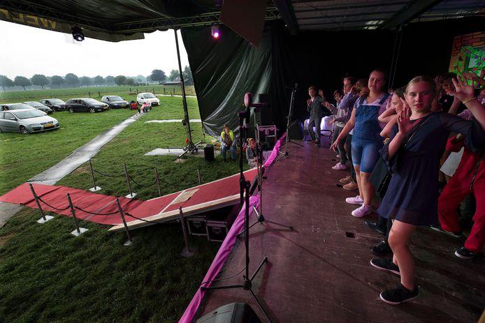Kinderen van groep 8 van basisschool de Klimtoren uit Drempt geven hun eindmusical midden in een weiland in Achter-Drempt. Ouders kijken toe vanuit auto's.