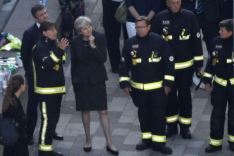 Premier Theresa May praat met brandweerlieden nabij de Grenfell Tower Beeld afp