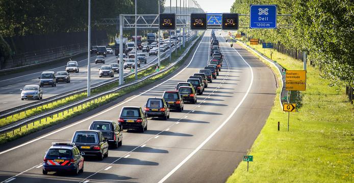 De colonne met lijkwagens passeert. In totaal 40 lijkwagens met een politie-escorte brengen de kisten vanaf Eindhoven naar Hilversum over de snelwegen A2 en A27.