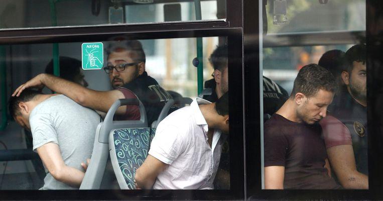 Turkse agenten begeleiden een bus vol opgepakte soldaten na de mislukte coup (Archiefbeeld).
