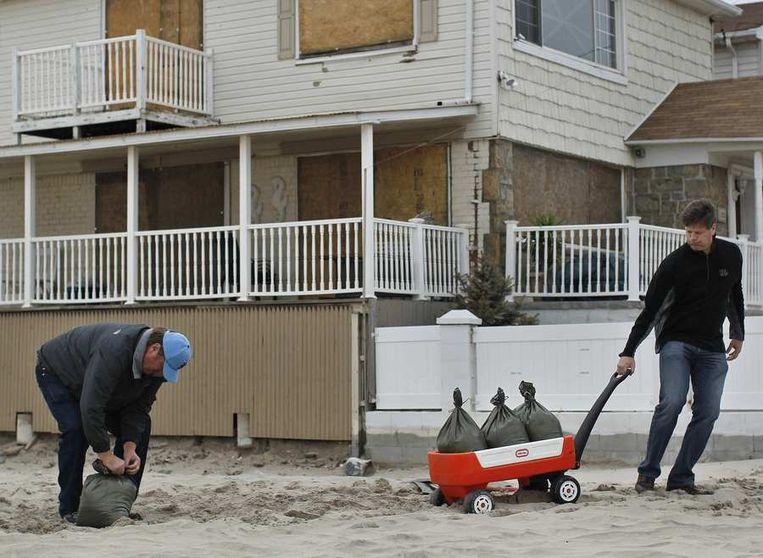 Inwoners van Queens vullen zandzakjes op Rockaway beach.