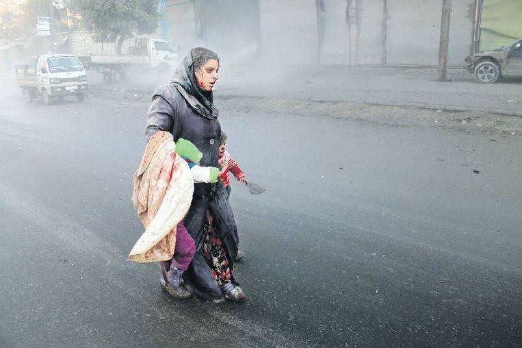 Aleppo, 15 december: een vrouw met haar kinderen, na een bombardement op een wijk in handen van de rebellen. Beeld afp