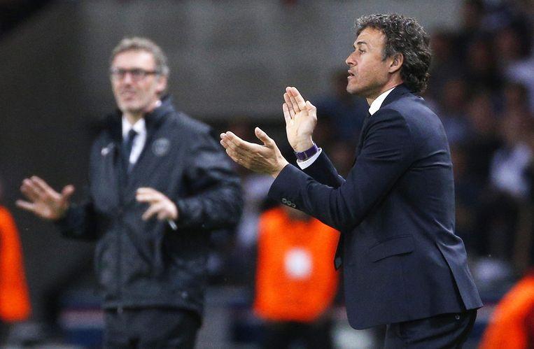 Barcelona- trainer Luis Enrique moedigt zijn ploeg aan in de Champions League. Op de achtergrond PSG- trainer Laurent Blanc. Beeld anp