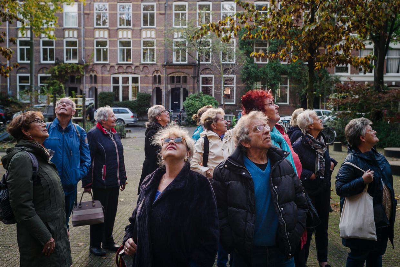 Gids Anke Wartenbergh (midden, witte jas) geeft leden van de Vereniging Ons Amsterdam een rondleiding over het WG-terrein in Oud-West. 'Het was er de hel op aarde.' Beeld Marc Driessen