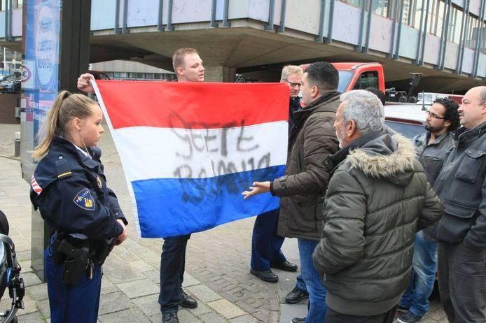 Een man met Nederlandse vlag met de tekst 'Geert bedankt' laat buiten het politiebureau een tegengeluid horen.