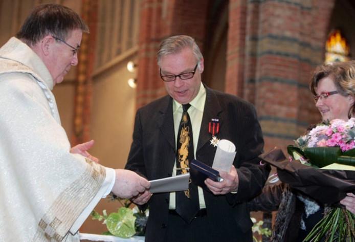 Pastoor Erpelinck reikt de oorkonde die hoort bij de Sylvesterorde uit aan Carolus Roelandt, met aan zijn zijde zijn echtgenote. foto Camile Schelstraete