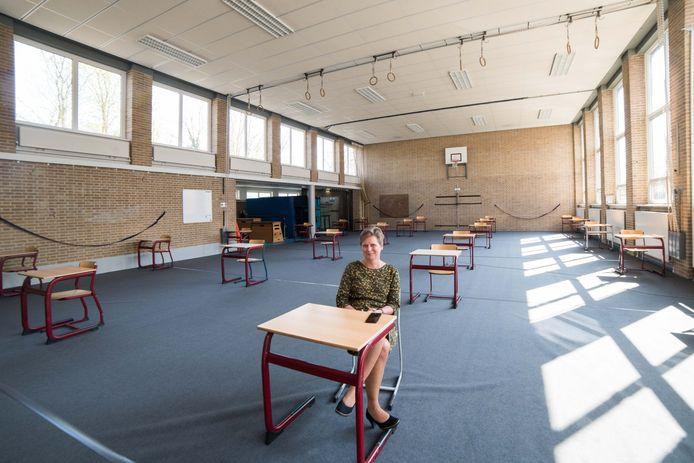 De tafels voor de examentoetsen staan bij Christelijik College Nassau Veluwe in Harderwijk flink ver uit elkaar. Rector Elly Bakker inspecteert de situatie: ,,Het doet zeer zo'n lege school.''